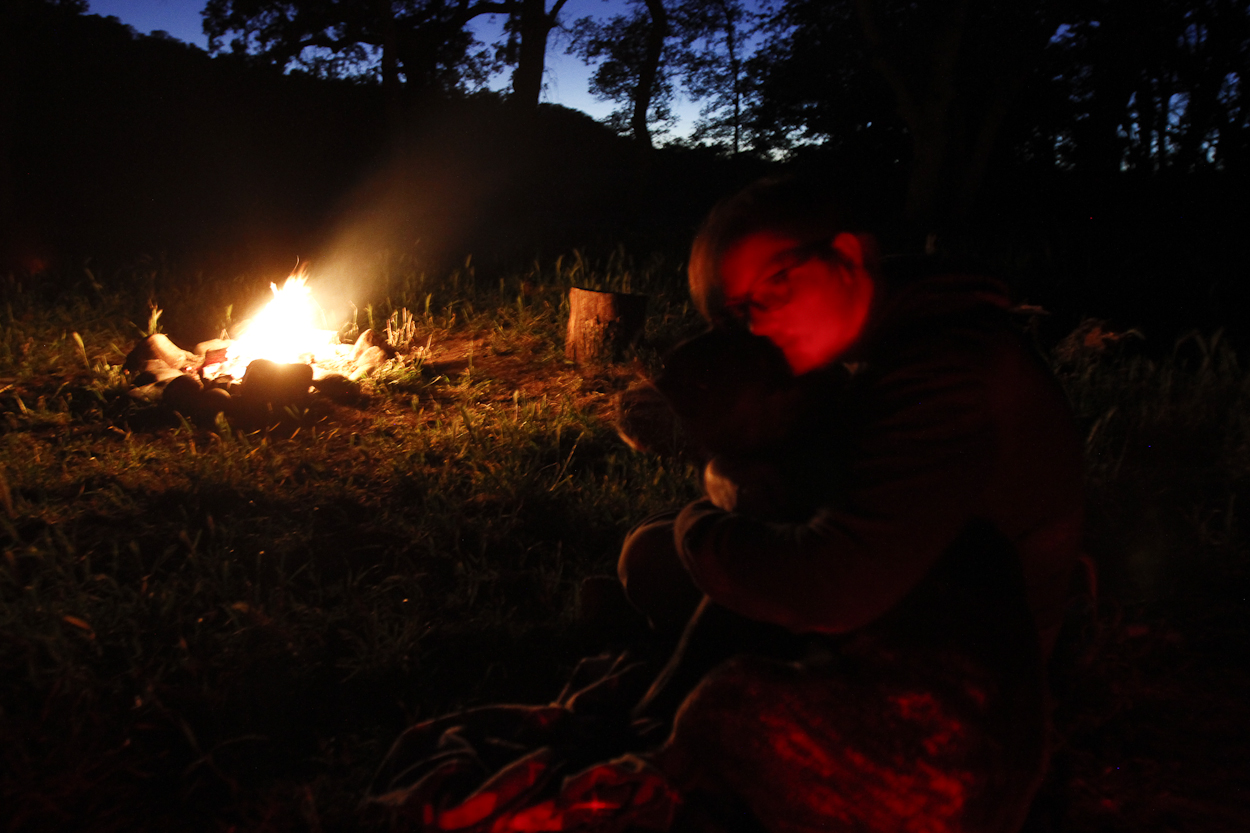 Melissa and Peaches curl up next to the campfire at Massacre Flat along the Sacramento River. Photo by Clay Duda.