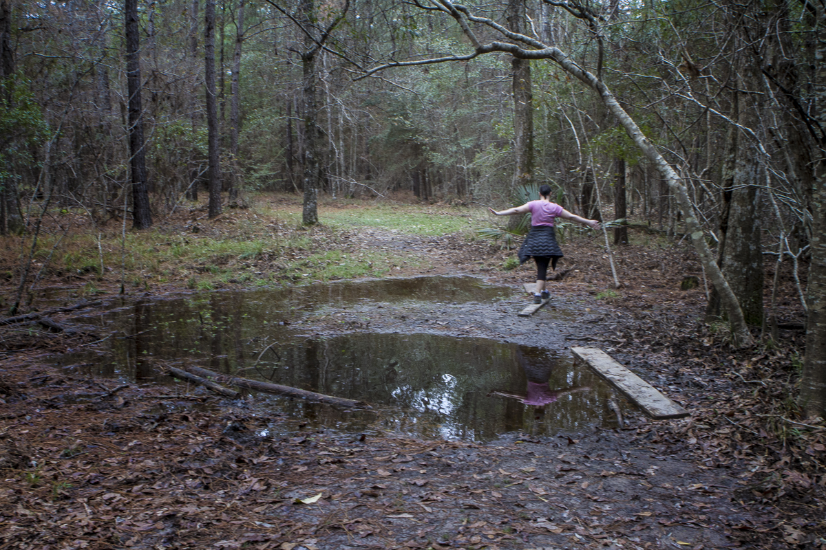 Melissa Duda skirts a puddle on the trail to Cane Bayou at Fontainebleau State Park near New Orleans. Photo by Clay Duda.